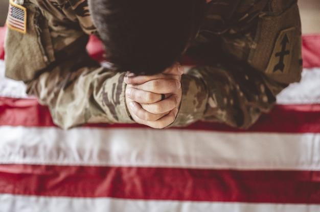 Soldado americano lamentando e orando com a bandeira americana na frente dele