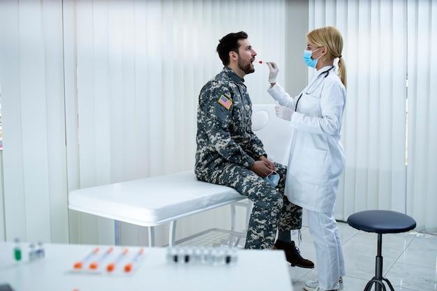 Soldado americano uniformizado fazendo teste pcr no consultório médico durante a epidemia do vírus covid19