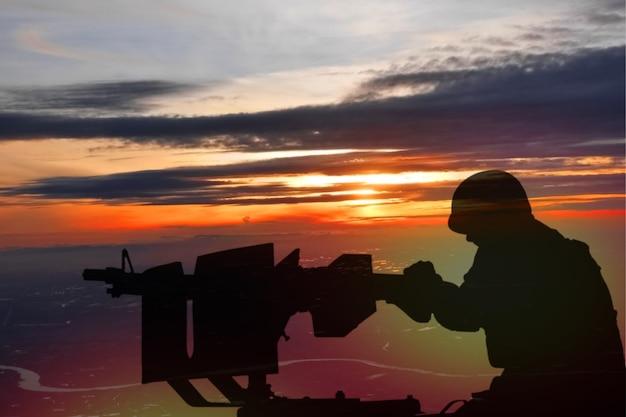 Soldado armado militar com metralhadora militar com o nascer do sol na cidade, guerra civil