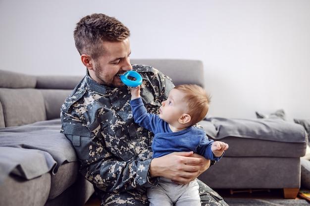 Soldado barbudo atraente sentado no chão da sala de estar, segurando seu amado menino adorável, segurando um mordedor na boca e brincando com ele.