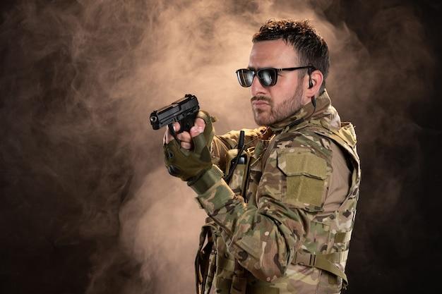 Soldado camuflado apontando a arma para a parede escura