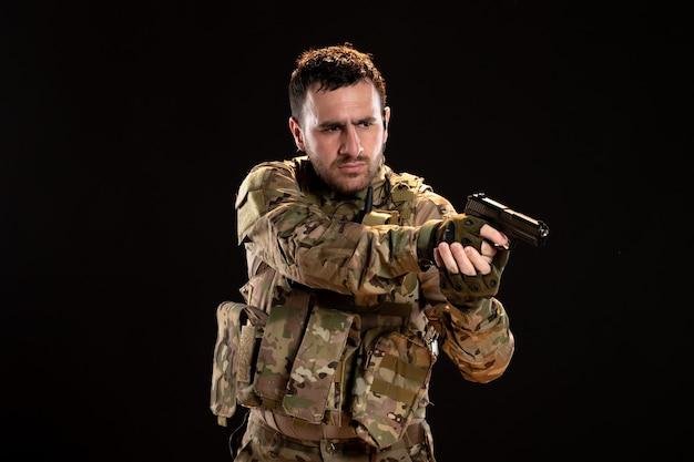 Soldado camuflado apontando arma na parede preta