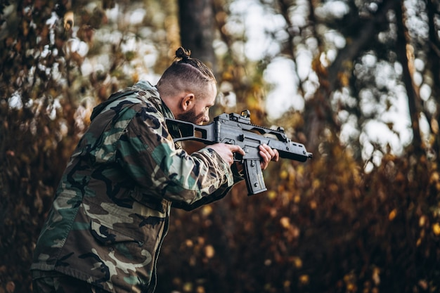 Soldado camuflado com rifle e rosto pintado, jogando airsoft ao ar livre na floresta