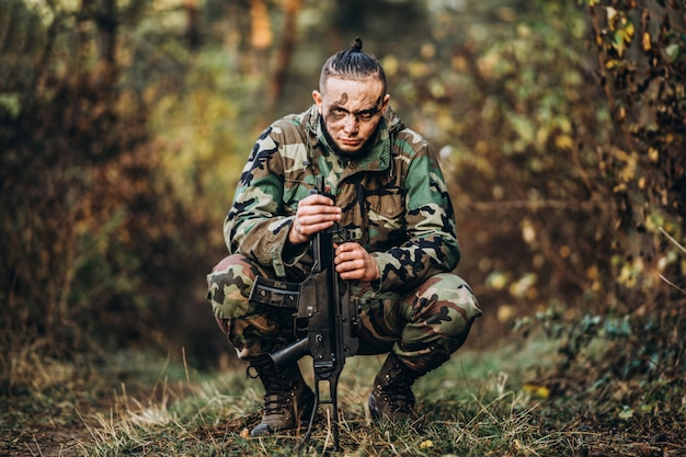 Soldado camuflado com rifle e rosto pintado, sentado na grama.