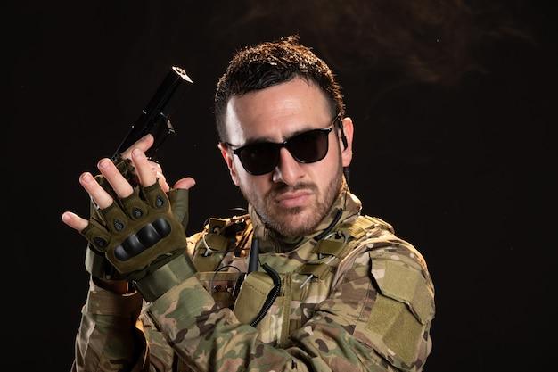 Soldado camuflado segurando arma na parede escura