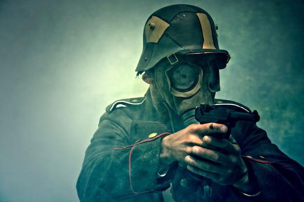 Soldado com máscara de gás aponta sua arma.