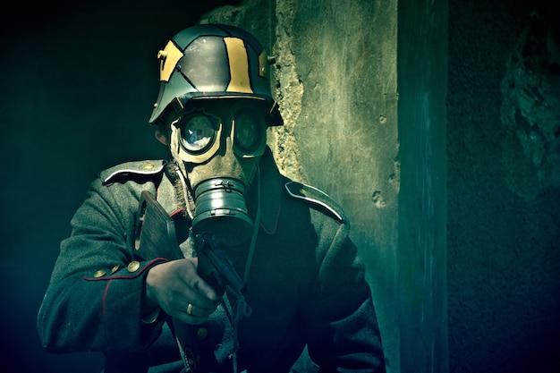Soldado com máscara de gás aponta sua arma. Foto Premium