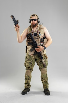 Soldado das forças especiais com o rifle no fundo branco.