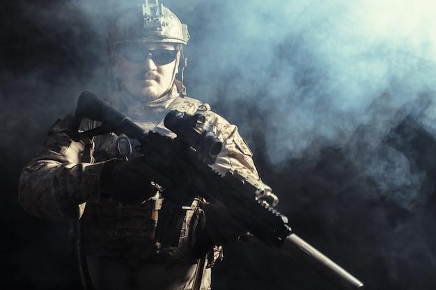Soldado das forças especiais com rifle na superfície escura