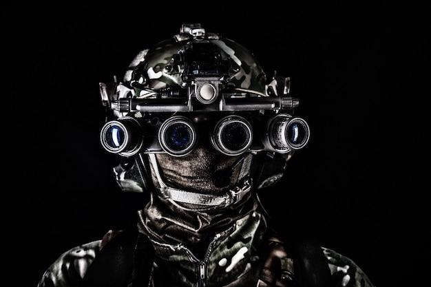 Soldado das forças especiais do exército moderno, lutador do esquadrão anti-terrorista, guerreiro do comando de elite usando máscara, usando óculos de visão noturna de quatro lentes em condições de pouca luz, fotos de estúdio em fundo preto