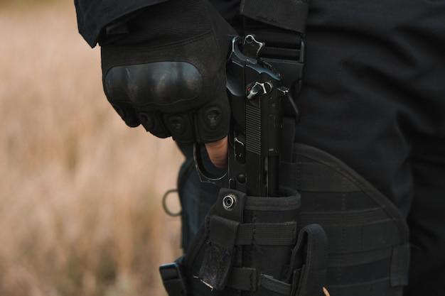 Soldado das forças especiais em uniforme preto tirando uma pistola do coldre
