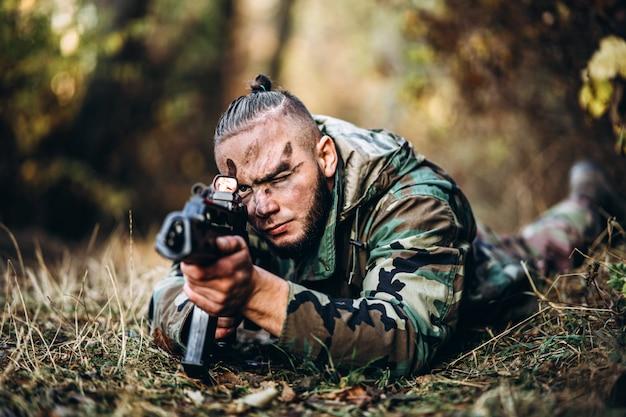 Soldado de camuflagem com rifle e rosto pintado, deitado na grama, apontando para o rifle.