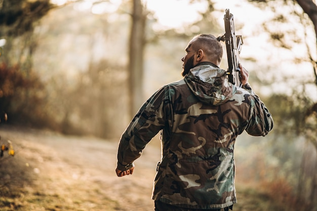 Soldado de camuflagem jogando airsoft ao ar livre na floresta
