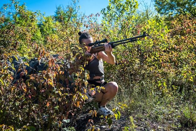 Soldado de mulher sexy segurando um rifle, olhando para longe na natureza. guerreira
