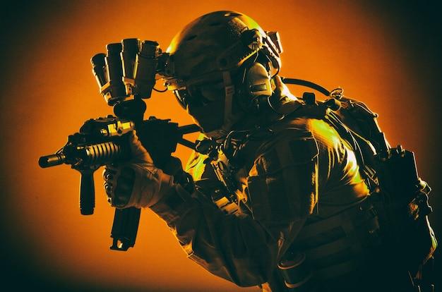 Soldado de operações especiais do exército, lutador de comando com munição tática completa, capacete com fone de ouvido de rádio e dispositivo de visão noturna, mirando rifle de assalto de cano curto na escuridão, tiro em estúdio discreto