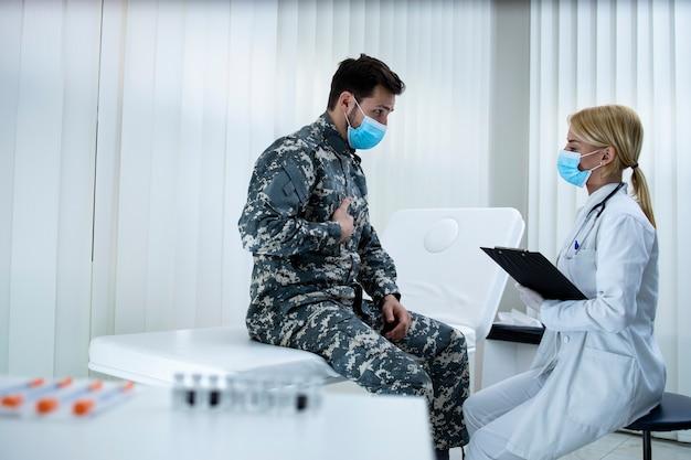 Soldado de uniforme com máscara facial reclamando de dores no peito ao médico