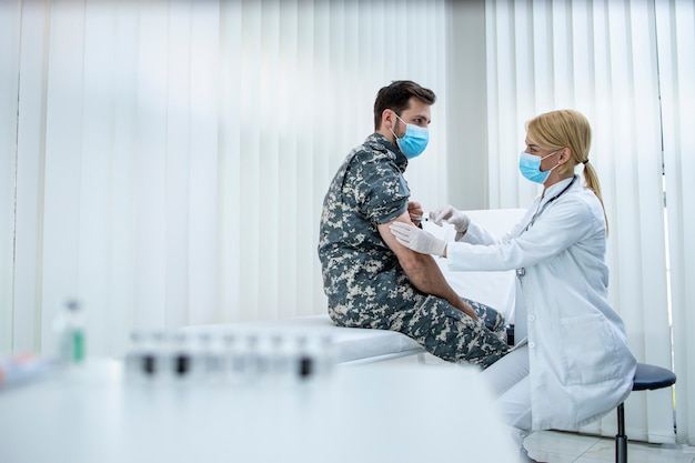 Soldado de uniforme recebendo vacina contra o vírus corona na clínica