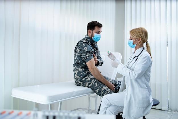 Soldado de uniforme recebendo vacina durante a pandemia do vírus corona