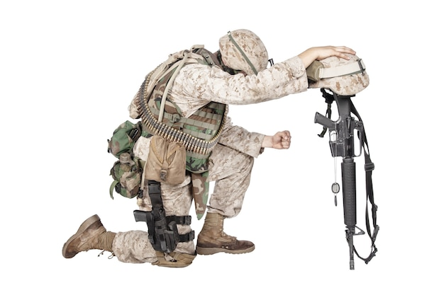 Soldado do exército em tristeza pelo camarada caído, de pé sobre o joelho, apoiando-se no rifle com capacete e duas placas de identificação na corrente, fotos de estúdio isoladas em branco. honras fúnebres militares, luto por mortos em combate