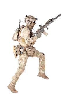 Soldado do exército, soldado de infantaria equipado, jogador de airsoft em uniforme de camuflagem de batalha, capacete e fone de ouvido tático de rádio pulando, correndo com rifle de assalto na mão.