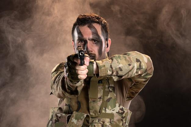 Soldado do sexo masculino camuflado apontando a arma na parede escura e esfumaçada