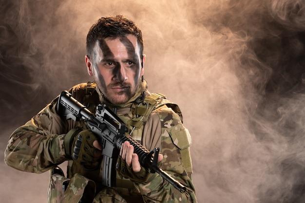 Soldado do sexo masculino camuflado com metralhadora na parede escura e esfumaçada