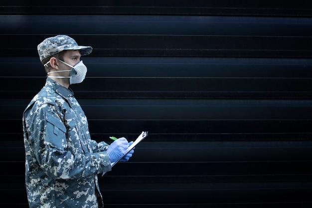 Soldado em uniforme de camuflagem usando luvas de proteção e máscara escrevendo notas contra um fundo preto