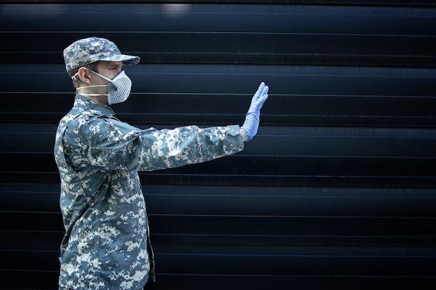 Soldado em uniforme de camuflagem usando luvas de proteção e máscara mostrando um sinal de pare com a mão contra um fundo preto