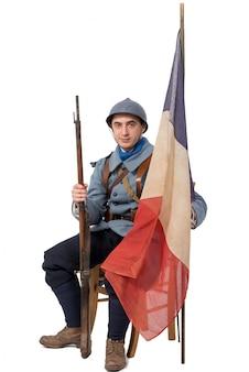 Soldado francês, sentado com a bandeira, isolada no branco