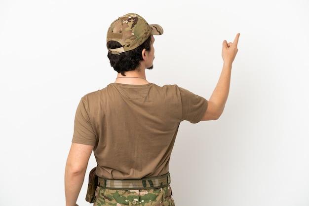 Soldado isolado no fundo branco apontando para trás com o dedo indicador