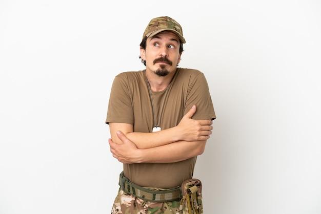 Soldado isolado no fundo branco fazendo gestos de dúvida enquanto levanta os ombros