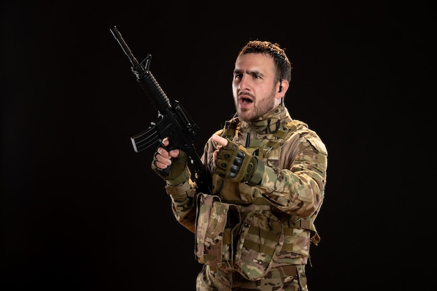 Soldado masculino camuflado segurando uma metralhadora no tanque militar do guerreiro de parede negra