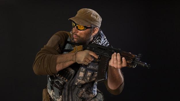 Soldado mercenário com uma arma olhando ao lado. conceito moderno de exército privado.