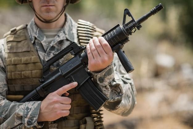 Soldado militar confiante em pé com um rifle no campo de treinamento