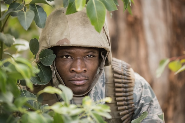 Soldado militar escondido atrás de árvores no campo de treinamento