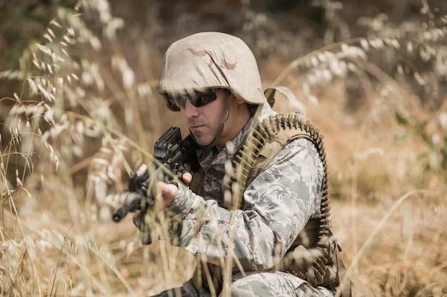 Soldado militar escondido na grama enquanto guarda com um rifle no campo de treinamento