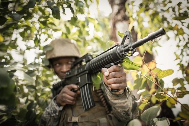 Soldado militar guardando com um rifle no campo de treinamento