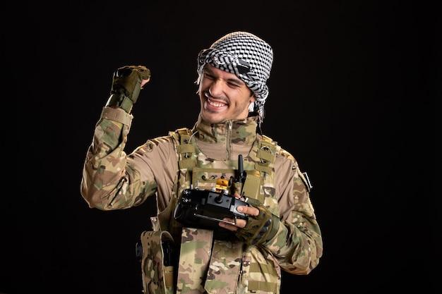 Soldado palestino alegre usando o controle remoto na parede preta