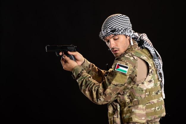Soldado palestino apontando arma para a parede preta