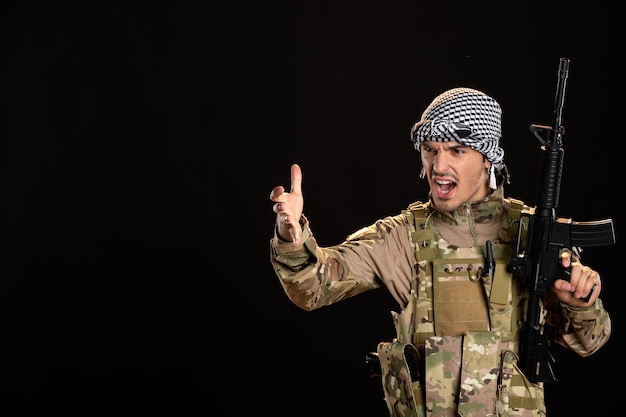 Soldado palestino camuflado com metralhadora em um tanque de superfície preta na palestina de guerra