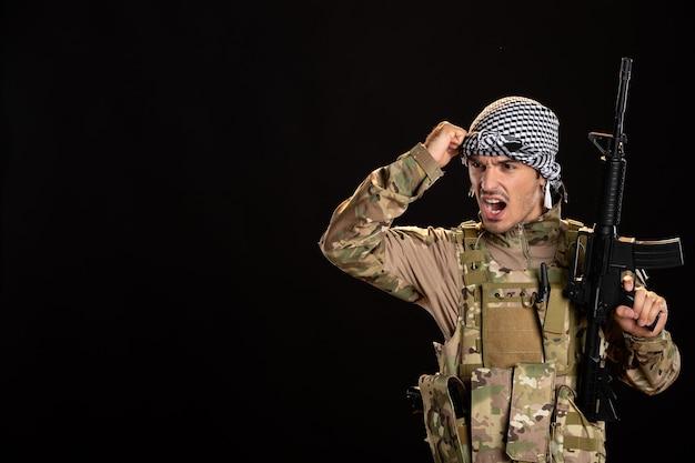 Soldado palestino camuflado com metralhadora no tanque de mesa preto na palestina de guerra