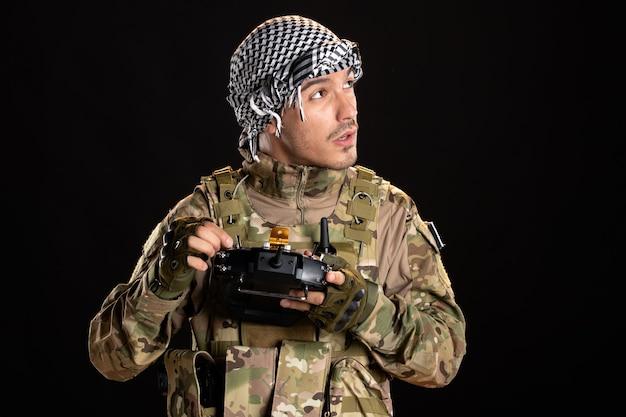 Soldado palestino consertando controle remoto em parede preta