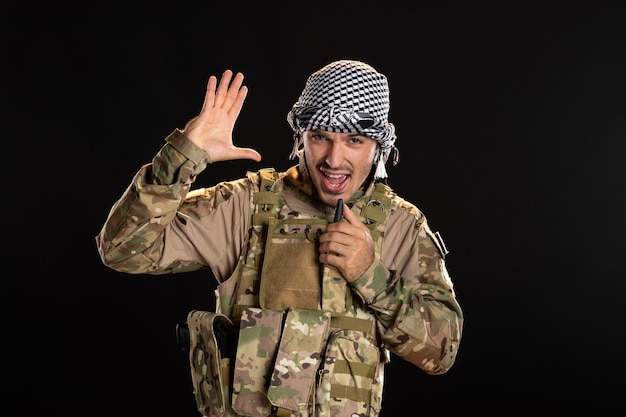 Soldado palestino em uniforme militar falando através da parede preta do rádio