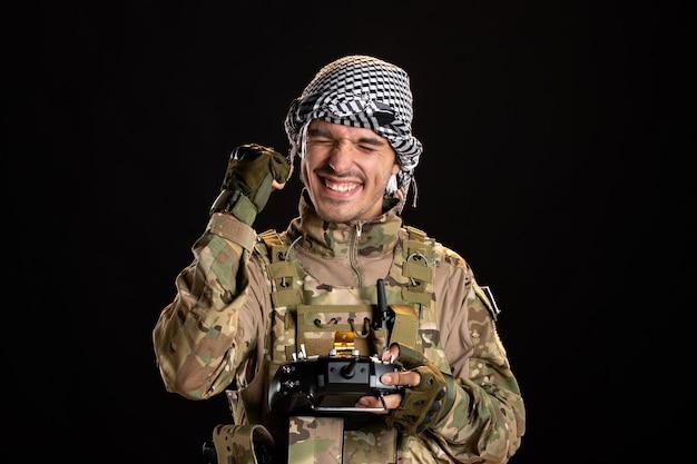 Soldado palestino feliz usando o controle remoto na parede preta