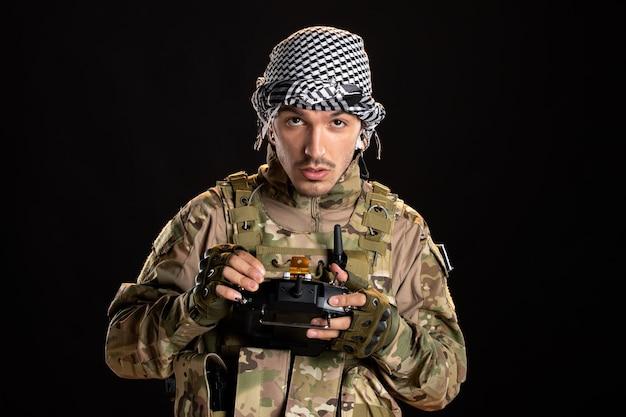 Soldado palestino usando controle remoto na parede preta
