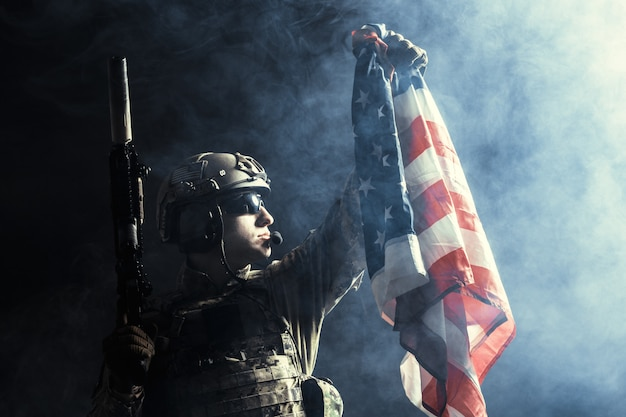 Soldado segurando a metralhadora com a bandeira nacional