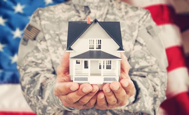 Soldado segurando uma maquete de casa