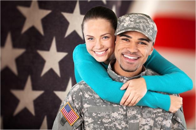 Soldado sorridente com sua esposa em pé contra o fundo da bandeira americana