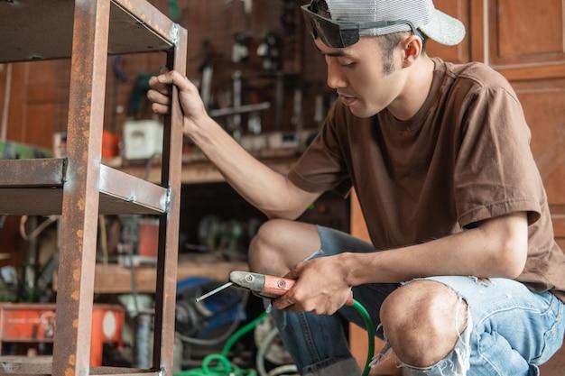 Soldador asiático segura uma grade de ferro ao soldar usando um soldador elétrico em uma oficina de soldagem