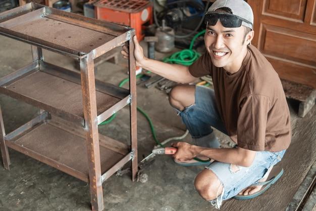 Soldador asiático sorri para a câmera segurando uma prateleira de ferro enquanto solda usando um soldador elétrico em uma oficina de soldagem